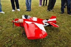 Aircraft model landed. Red and white radio controlled aircraft with methanol engine on a grassy field stock photography