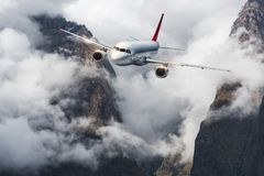 Aircraft, mountains in overcast sky. Airplane Royalty Free Stock Photo