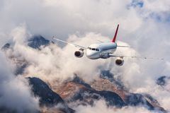 Aircraft, mountains in overcast sky. Airplane Stock Image