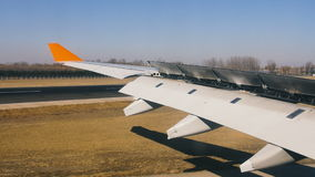 Aircraft move by air strip at airport, wing view from the inside stock footage