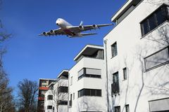 Aircraft noise and commercial wide-body aircraft over houses. Large-capacity aircraft over residential buildings produces aircraft noise royalty free stock photography