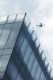 Aircraft over office tower Royalty Free Stock Photo