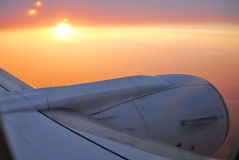 Aircraft over sunset sky. View to sunset sky and sun from the aircraft with the detail of wing and turbine Royalty Free Stock Image