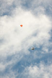 Aircraft and parachute on a background of clouds. Stock Photo