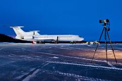 The aircraft is parked at the airport at night and the camera is on a tripod. The aircraft is parked at the airport at night and the camera is on a tripod Stock Photo