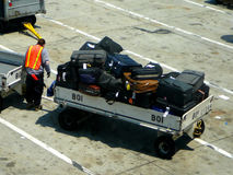 Aircraft passenger luggage. Worker loading aircraft luggage into cart Stock Photography