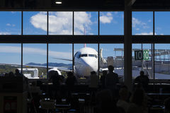 Aircraft and people in the airport cafe concept. View of aircraft and people in the airport cafe in silhouette Royalty Free Stock Photography