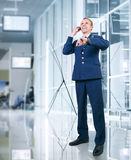 Aircraft pilot talking by phone in airport area Royalty Free Stock Photos