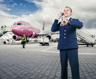 Aircraft pilot talking by phone on airport runway before flight Stock Photo