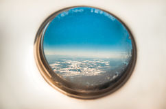 Aircraft porthole with views to the Alps Stock Photos