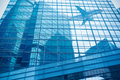 Aircraft reflected in the building curtain wall Stock Photos