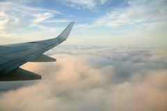 Aircraft right side wing, airplane flying. Over clouds in a blue sky day Stock Image