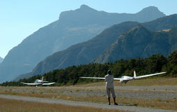 Aircraft on runway. Rear view of person watching light aircraft on runway with mountainous background Royalty Free Stock Photography
