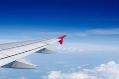 Aircraft's wing in blue sky above white clouds Stock Photography