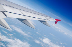 Aircraft's wing in blue sky above white clouds Stock Photo
