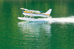 Aircraft seaplane taking off on calm water of lake Stock Images