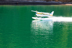Aircraft seaplane taking off on calm water of lake Royalty Free Stock Image