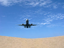 Low flying aircraft over beach. Low flying aircraft in blue sky over sandy beach Royalty Free Stock Image