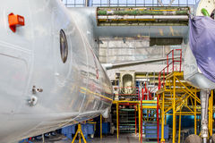 Aircraft stands on repair in aviation hangar. Back view of white aircraft stands on repair in aviation hangar. Airplane without wing placed in front of yellow Royalty Free Stock Images