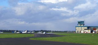 Aircraft taxiing in front of a control tower in an airport Stock Images