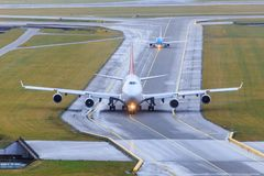 Aircraft taxiing on taxiway. Boeing 747 and Embraer 175 taxiing behind each other on taxiway royalty free stock image