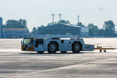 Aircraft tow tractor with moving tug. On the airport apron royalty free stock photography