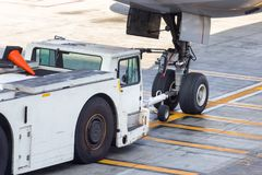 Airplane tow truck hooked up on the front landing gear. An aircraft tow truck is connected to the tug of the nose landing gear, closeup Royalty Free Stock Photography