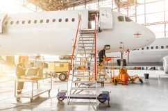 Aircraft is under repair, technical inspection is a working technician. A view of the nose, a cockpit of pilots with a staircase l. Eading into the entrance Royalty Free Stock Images