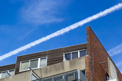Aircraft vapour trail over an apartment block Stock Images