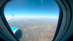 Aircraft window with the land shown from it. HD stock video footage