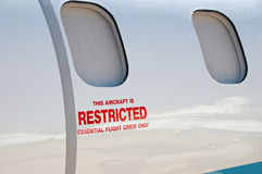 Aircraft windows. Close up of a special purpose lear jet with Restricted signage royalty free stock image
