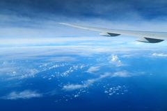 Aircraft wing above the clouds, view from the airplane window Stock Photography