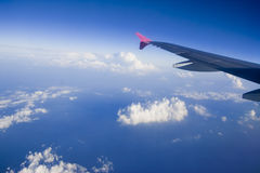 Aircraft wing on a blue sky. Aircraft wing flying high above the clouds Stock Photography