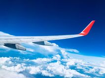 Aircraft wing on blue sky background and white cloud below, seeing from window plane Royalty Free Stock Photo