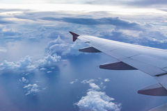 Aircraft wing on the clouds, flying evening background Stock Photography