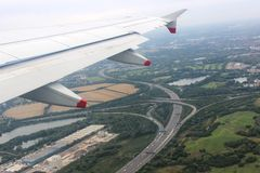 Aircraft wing in flight over motorway junction. View from an aircraft in flight from London to Manchester with a wing of the aircraft at the left and a busy royalty free stock photo