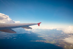 Aircraft wing flying over clouds Royalty Free Stock Photo