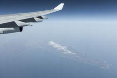 Aircraft wing over islands in ocean Royalty Free Stock Photos
