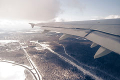 Aircraft wing over winter snow landscape with trees and highways Royalty Free Stock Images