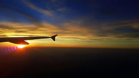 Aircraft wing in the sky sunrise. Aircraft wing in the sky on a beautiful colorful sunrise Panorama Royalty Free Stock Photo