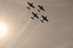 Aircrafts formation. Aircrafts flying in formation shot from below against sky and sun Royalty Free Stock Photography
