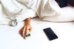 Aire acondicionado remoto del control de la mano del hombre joven y el dormir en el b fotos de archivo libres de regalías