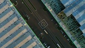 Aire d'atterrissage vertical d'hélicoptère de vue aérienne entre de grands entrepôts clips vidéos