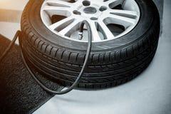 Aire de relleno en un neumático de coche - blanco y negro y filte de la luz del sol Fotos de archivo