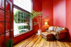 Aire de repos avec les murs rouges, la grande fenêtre et le sofa de cuir Images libres de droits