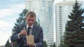 Aire libre de Eating Chinese Noodles del hombre de negocios almacen de metraje de vídeo