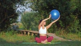 Aire libre de la aptitud, mujer joven que hace los ejercicios para los músculos del brazo con la bola grande de la aptitud que se almacen de metraje de vídeo