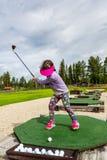 Aire libre de la chica joven en un campo de prácticas que juega a golf y practicar su oscilación imagen de archivo libre de regalías