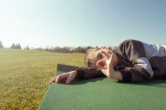 Aire libre del sueño del muchacho en el parque del otoño imagen de archivo