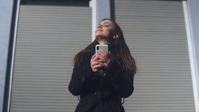 Aire libre derecho femenino joven que concierta la cita en el teléfono, aire fresco que huele metrajes